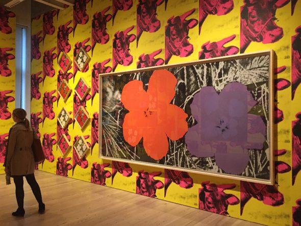 """Werk aus der Serie """"Flower"""" und die Kuh-Tapete """"Cow Wallpaper"""" von Andy Warhol in der Ausstellung """"Andy Warhol - From A to B and Back Again"""" im Whitney Museum in New York"""