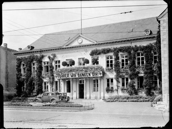 """Frontalaufnahme des Rathausplatzes Eupen mit dem Banner """"Führer wir danken dir"""" (Bild: Staatsarchiv)"""