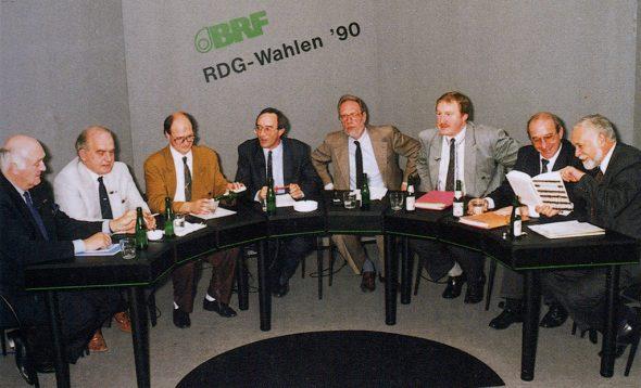 RDG-Wahlen 1990 (v.l.n.r.): Fred Evers (PFF), Kurt Ortmann (CSP), Oswald Schröder (PFF), Paul Maraite (BRF), Martin Steins (BRF), Karl-Heinz Lambertz (SP), Gerhard Palm (PDB), Josef Benker (Ecolo) (aus: 60 Jahre BRF, S. 181)