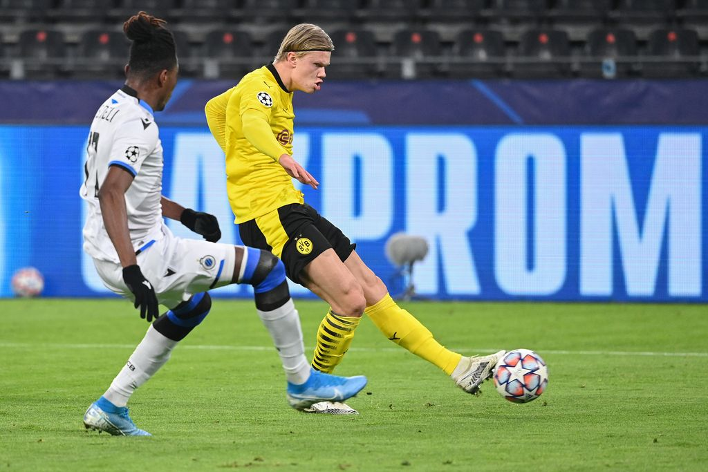 Dortmund's Norwegian forward Erling Braut Haaland (R) gets past Club Brugge's Ivorian defender Simon Deli to score the opening goal during the UEFA Champions League group F football match BVB Borussia Dortmund v Club Brugge in Dortmund, western Germany, on November 24, 2020. (Photo by Ina Fassbender / AFP)
