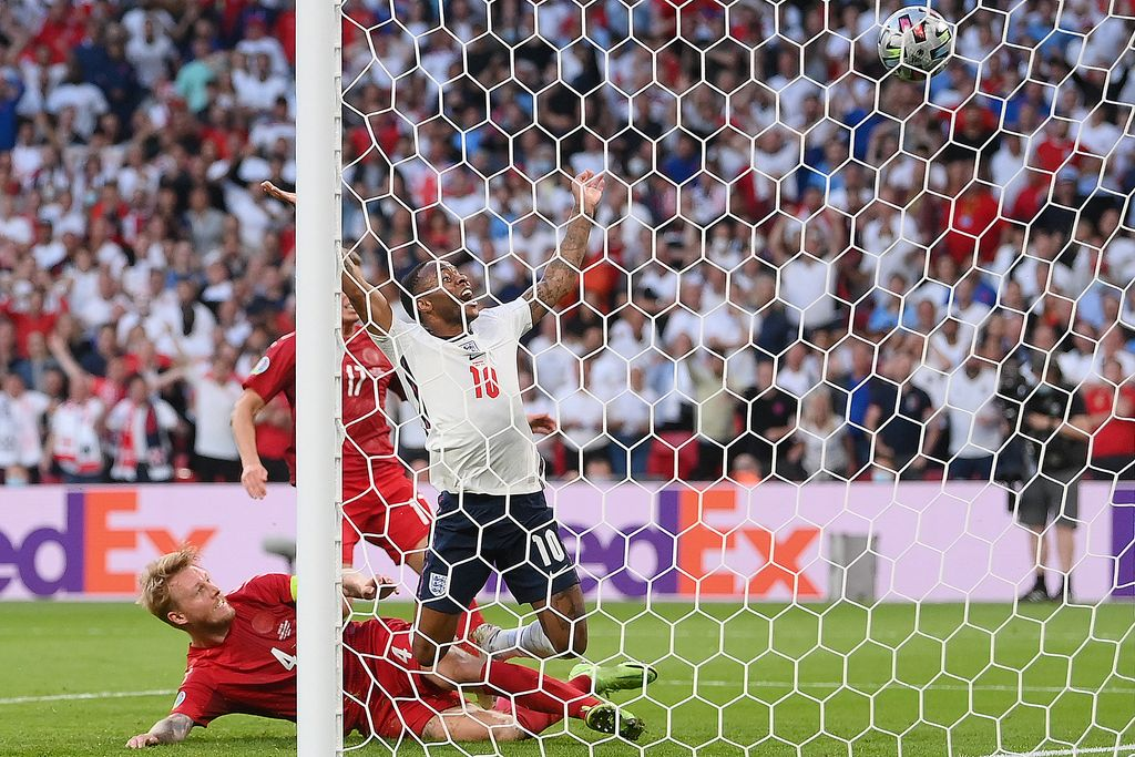 England's forward Raheem Sterling (R) celebrates scoring his team's first goal during the UEFA EURO 2020 semi-final football match between England and Denmark at Wembley Stadium in London on July 7, 2021. (Photo by Laurence Griffiths / POOL / AFP)