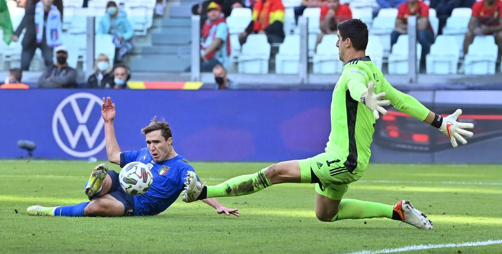 Italian Federico Chiesa and Belgium's goalkeeper Thibaut Courtois pictured in action during a soccer game between Belgian national team Red Devils and Italy, the Nations League third-place play-off, in Torino, Italy, on Sunday 10 October 2021. BELGA PHOTO DIRK WAEM